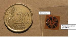 """Fig. 3 - Un tipico estensimetro per tensioni residue: si tratta del modello Micro-measurement EA-06- 062RE-120 , uno dei modelli per cui le equazioni per la trasformazione delle deformazioni rilevate in tensioni residue sono disponibili nella normativa ASTM E 837 e nella """"TN 503 – Measurement of residual stress by the hole drilling train gauge method"""". L'attenuazione della deformazione rilasciata all'aumentare della distanza dal foro rende opportuno l'utilizzo di estensimetri dalle dimensioni quanto più possibili ridotte."""